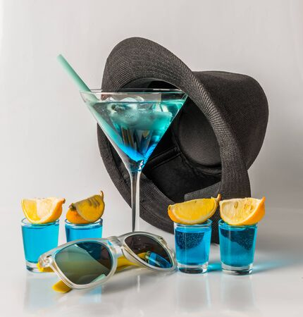 Colorful drink in a martini glass, blue and green combination, four drinks in a shotglass, black hat, sunglasses, party set
