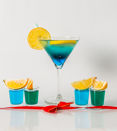 Colorful drink in a martini glass, blue and green combination, four drinks in a shotglass,red bow, party set