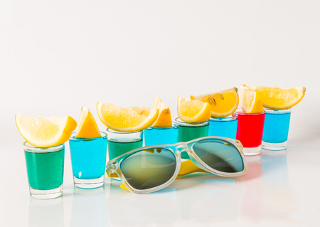 Glasses with blue, green and red kamikaze, glamorous drinks, mixed drink poured into shot glasses, sunglasses, party set Stock Photo