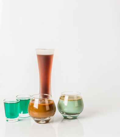 Five color drink shots, different glass shapes, green and brown shots, party set