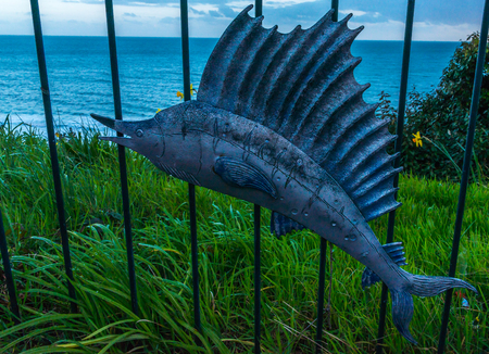 The metal ornament on a balustrade in a seaside village, symbolic in the shape of a fish, ocean and plains