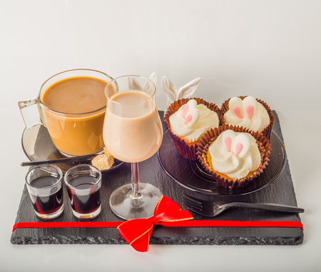 White coffee in modern glass cup, muffins with Easter decoration, red bow, milk drink, coffee set