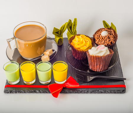 White coffee in modern glass cup, muffins with Easter decoration, red bow, interesting bunny napkin, milk drink, coffee set