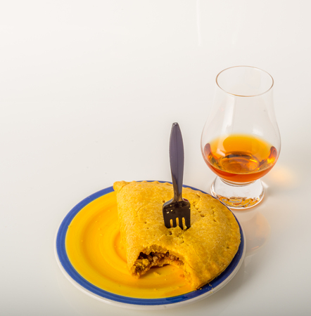 single malt tasting glass, single malt whisky in a glass, white background, jamaican food, pattie, cactus