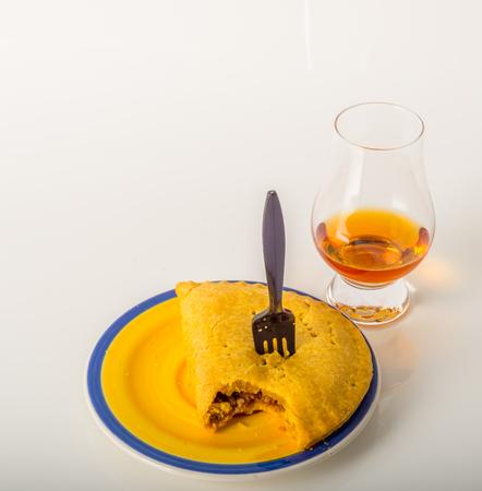 single malt tasting glass, single malt whisky in a glass, white background, jamaican food, pattie, cactus