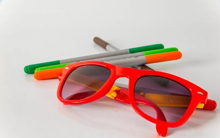 fluorescence: Marker pens, red, green, orange and brown, set color  highlighters, sunglasses, school tools Stock Photo