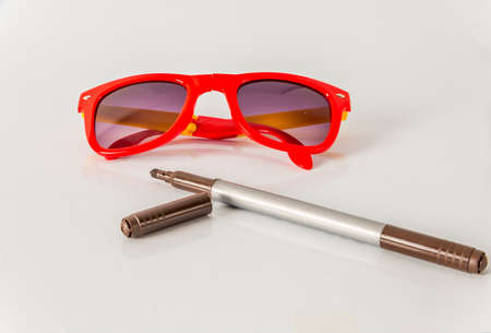 fluorescence: Brown marker pen  with red sunglasses, color  highlighter, school tools, white background Stock Photo