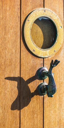 door knob: Old wooden door to house with a brass knocker in the shape of a fish and a bull`s eye, sea element, vintage decor Stock Photo