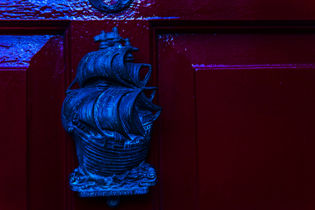 Old wooden door to house with brass knocker shaped sailing  ship with inscription of 16 century galeon, sea element, vintage decor
