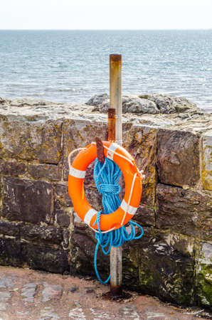 Orange lifebuoy on a stone wall rescue, blue rope, ocean shore, safety