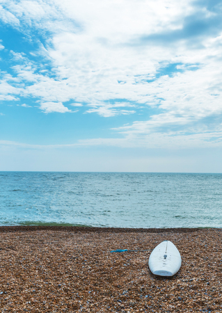 Surfboard on the pebble beach and the ocean, waves and blue sky, sunny day Stock Photo