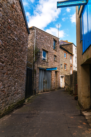 Narrow passage from the back of buildings in seaside town, old architecture, stone walls, historic buildings, english town