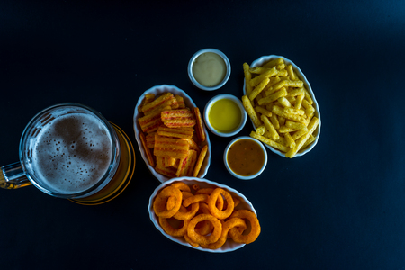 Set of snacks with dip and pint of beer, crunchy snacks, good food, black background