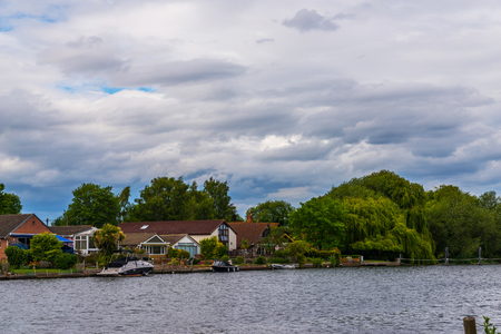Wide river and houses on the shore, moored boats, green vegetation, a place of relaxation in the city, clouds Stock Photo