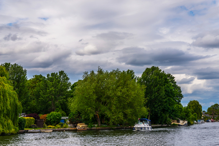 Wide river and houses on the shore, moored boats, green vegetation, a place of relaxation in the city, clouds Stock Photo - 80271285
