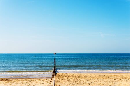 Dock pilings on a sandy beach, blue ocean and yellow sand, sunny hot day in seaside resort, vacation