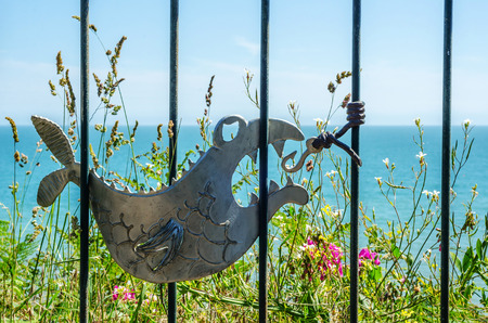metal ornament on a balustrade in a seaside village, symbolic in the shape of a fish, ocean and plains, decor