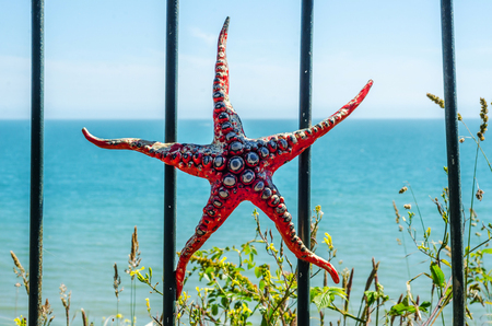 Metal ornament on a balustrade in a coastal town, a symbolic starfish shaped element, decor Stock Photo