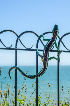 Metal ornament on a balustrade in a seaside village, symbolic lizard shaped element, decor