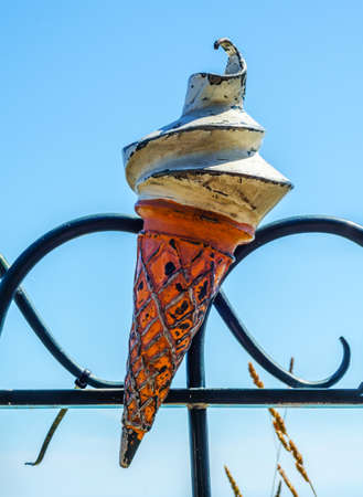 metal ornament on a balustrade in a seaside village, a symbolic element in the shape of ice cream in a wafer, decor