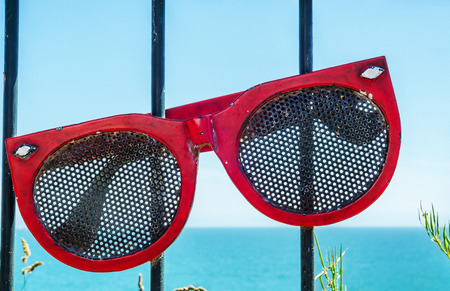 Metal ornament on a balustrade in a seaside town, symbolic element in the form of sunglasses, decor