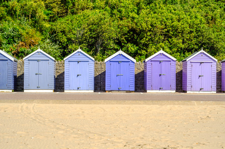 sunburnt: Colored houses on the beach, colorful door to summer cottages, seaside spot, sunny day Stock Photo