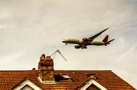 Passenger plane flying over the roofs of residential homes, low airplane flies, red roof tiles, transportation