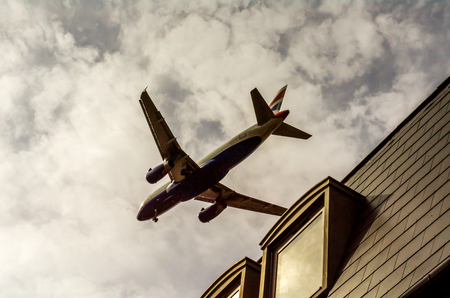 Passenger plane flying over the roofs of residential homes, low airplane flies,  roof tiles, transportation