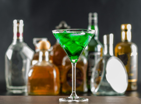 Colorful drink on the background of bottles in original shapes, cocktail drink with ice cubes, party night