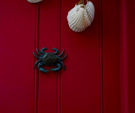 door handle: Brass crab knocker, knocker on red wooden door, decorative element, vintage