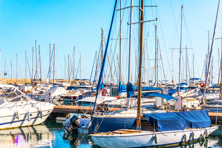 Beautiful luxury yachts and motor boats anchored in the harbor, hot summer day and blue water in the marina, blue sky, vacation