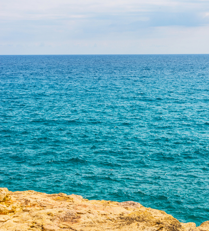 high cliff above the sea, summer sea background, many splashing waves and stone, sunny day Stock Photo