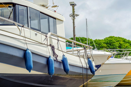 Boat on stand on the shore, close up on the part of the yacht, luxury ship, maintenance and parking place boat, marine industrial