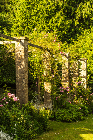 Beautiful park in antique style, stone decorations on pedestals, beautiful plants, resting place