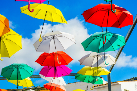 Colourful umbrellas urban street decoration. Hanging colorful umbrellas over blue sky, tourist attraction, sunny day