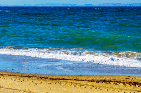 close up of the sea water affecting the sand on the beach, sea waves calmly flowing sand, relaxing view, summer time