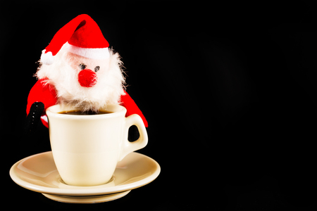 Black coffee in a white cup and plush Santa Claus, drink set, tasty drink Stock Photo