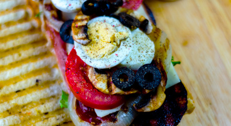 grilled sandwich with various cold meats, cheese, mushrooms, tomato and egg, tasty and healthy snack, hot food