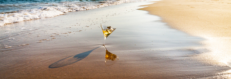 drink in a martini glass washed by sea water on a sandy beach, relax on the beach, refreshing drink during your vacation, summer time Stock Photo