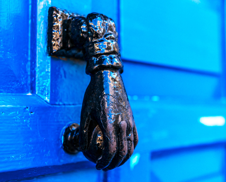 Door with brass knocker in the shape of a hand, beautiful entrance to the house, decor