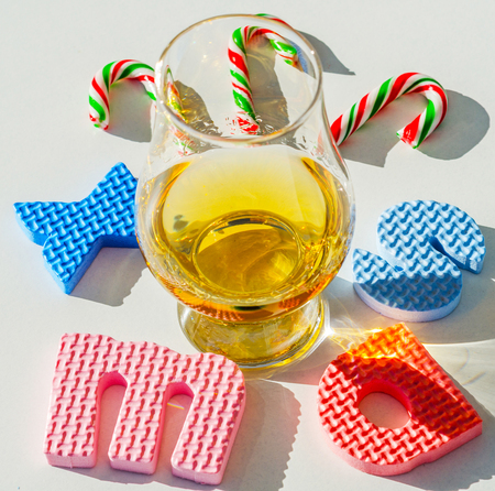 Single malt whisky in the glass with rubber letters, xmas inscription, luxurious tasting glass, drink set