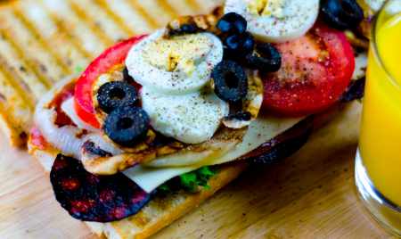 Grilled sandwich with various cold meats, cheese, mushrooms, tomato and egg, tasty and healthy snack, hot food Stock Photo