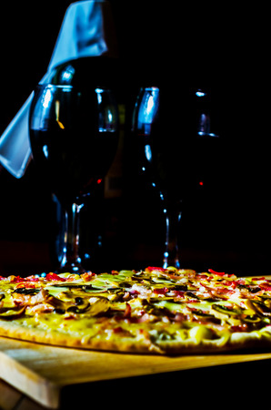 Red wine and delicious pizza with bacon, ham, mushrooms and mozzarella on a thin crust, tasty food