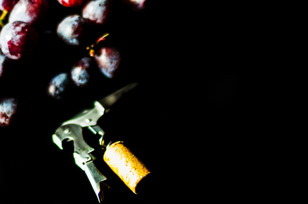 Corkscrew with cork on snail beside large red grape fruit on black background, winery