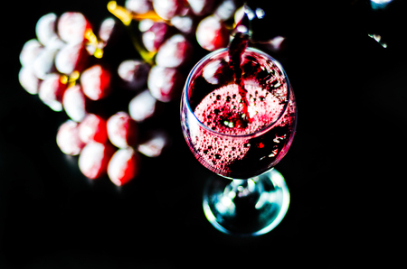 Pouring red wine in a glass, celebration of a moment with a glass of wine, exquisite liquor for gourmets, winery