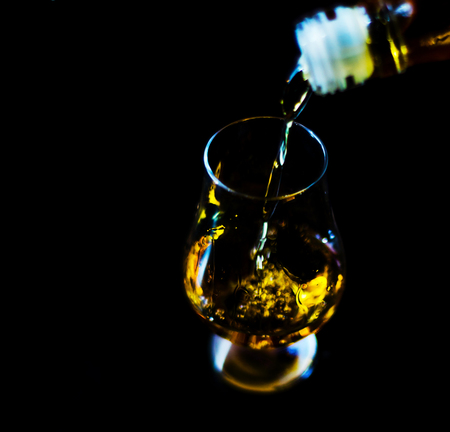 pouring single malt whisky into a glass, golden color whisky, an excellent drink to celebrate the moment