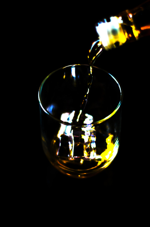 Pouring single malt whisky into a glass, golden color whisky, an excellent drink to celebrate the moment Stock Photo