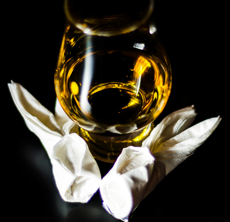 Single malt whiskey in a glass of tasting with napkin bunny, festive Easter decoration, holiday