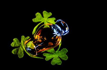 Single malt whisky in a glass of tasting with decoration for St. Patricks day, green clover symbol for Irish holiday, festive Stock Photo