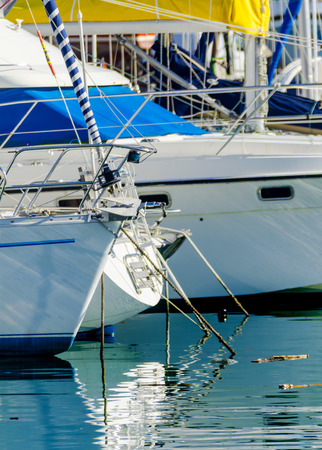 closeup on a yacht, yachts and motor boats anchored in a harbor, a hot day and blue water in a marina, blue sky, recreation